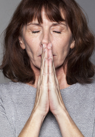 zen mature woman with brown hair and grey sweater meditating with praying hands,eyes closed, seeking for soothing peace and inner serenity Stock Photo