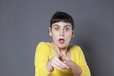 stunned: young brunette woman under shock staring at someone with finger pointing forward looking stunned and stressed out Stock Photo