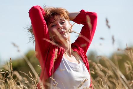 donne mature sexy: casuale relax femminile - tenore di donna matura che gode l'aria fresca tra i capelli con il fiore in bocca in alto campo estivo alla ricerca per la pace, la luce del giorno d'estate Archivio Fotografico