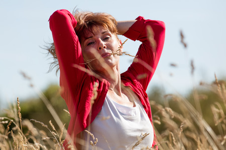 50s women: female casual relaxation - content mature woman enjoying fresh air in her hair with flower in her mouth in high summer field seeking for peace,summer daylight Stock Photo