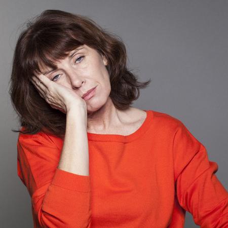 agotado: hermosa mujer mayor cerrando los ojos, en busca de la comodidad con la cara apoyada en las manos para dormir la siesta o durante las vacaciones de la menopausia