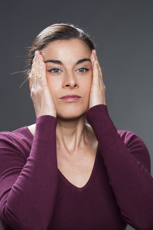 acupressure hands: beautiful 30s woman practising face acupressure  with hands on face and temples for natural eye care and facial contour exercise