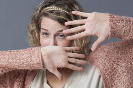 20s: surprise and fear concept - anxious 20s woman with short curly hair protecting herself with her hands,studio shot