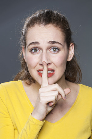 taboo: secret and taboo concept - scared 20s woman wearing yellow sweater asking for silence with finger on mouth,studio shot