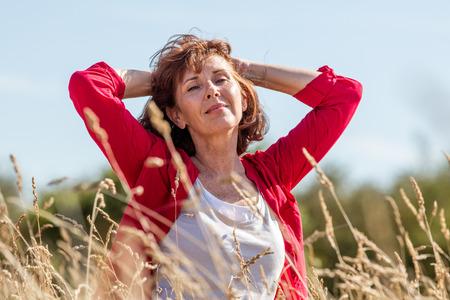 vrouwelijke ongedwongen ontspanning - lachende stralende volwassen vrouw genieten van de frisse lucht in haar haar, in harmonie met de natuur in de lange zomer grasveld op zoek naar vrede, de zomer daglicht