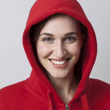 20s: closeup portrait of beautiful happy 20s woman wearing red hooded sweater for cool attitude
