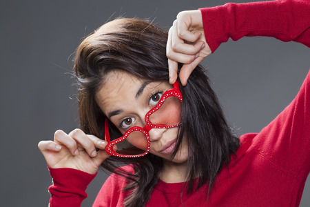 20s: cute smiling 20s woman looking over her red heart-shape glasses Stock Photo