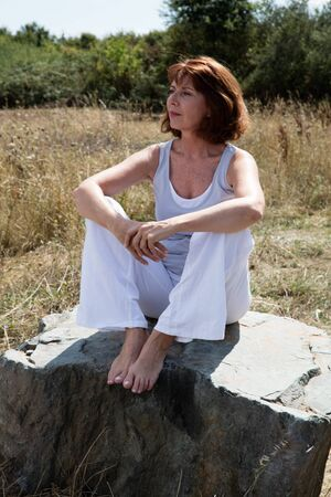 senior zen - relaxed 50s beautiful yoga woman sitting on a stone, wearing a yoga outfit for meditation and inner peace outdoors in summer daylight