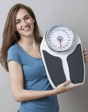 kilos: focused young woman smiling with weighting scale in hands