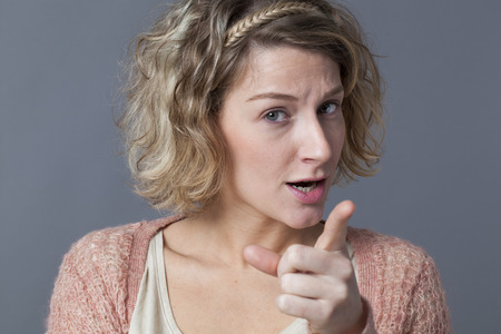 anxious 20s blonde girl showing her index finger for signal of stopping, forbidding or behaving with unhappiness