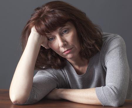 退屈または辞任のテーブル上に横たわる彼女の手で彼女の顔を休んで圧倒される年配の女性