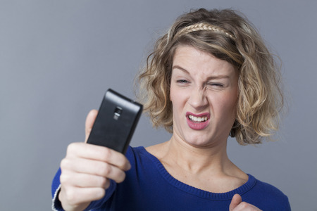 20's: 20s blonde girl disappointed about her image on smartphone Stock Photo