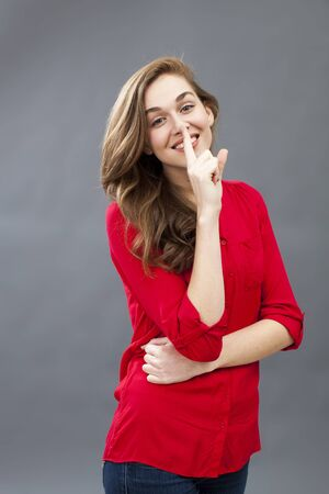 discretion: fun secret concept - gorgeous 20s woman wearing red shirt smiling in showing a finger on her lips for discretion,studio shot