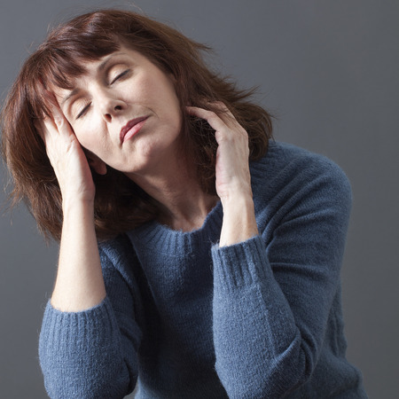 wellness sleepy: beautiful senior woman closing her eyes,seeking for relaxation with face leaning on hands to sleep or nap for menopause break Stock Photo