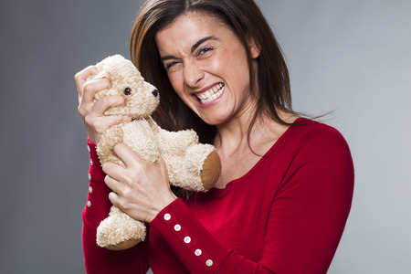 burnout: irritated young woman strangling teddy bear with violence for nervous breakdown or motherhood burnout