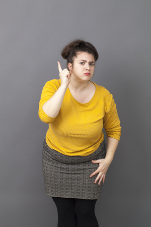blaming: teacher-like oversize young woman staring at someone with finger pointing forward with blaming attitude and self-assertion