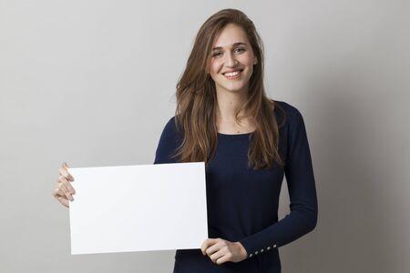 azul marino: hermosa joven llevaba azul marino sostiene una reclamaci�n a bordo de comunicaci�n en blanco