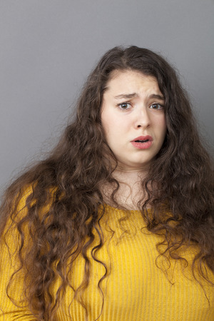 unhappiness: unhappiness and disappointment concept - scared young overweight woman with long brown hair expressing regret,willing to escape from danger,studio shot
