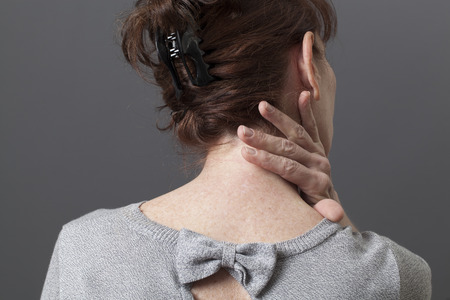 50s woman in back view with fatigue and tension in body