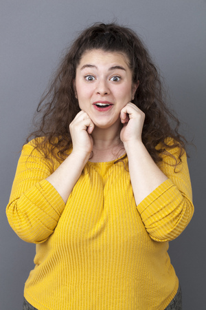20s: happy 20s big woman acting thrilled, wearing colorful sweater, expressing surprise and joy Stock Photo