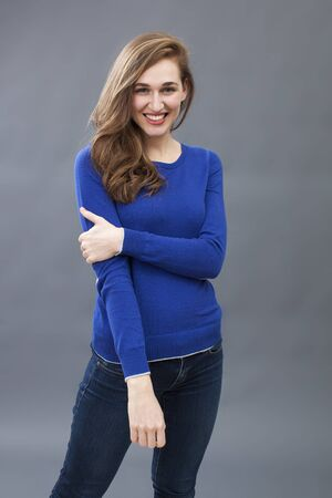 smiling beautiful young woman wearing blue sweater and jeans with a folded arm, expressing wellbeing and happiness Stock Photo
