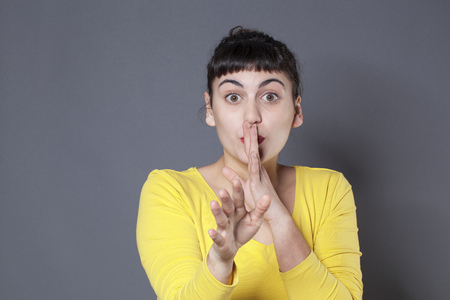 discretion: fun silence concept - cheeky 20s brunette girl wearing yellow sweater asking for discretion with a hand on mouth,studio shot Stock Photo