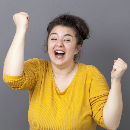 overweight girl: success concept - laughing young overweight girl wearing a yellow sweater expressing her achievement and joy with both hands up Stock Photo
