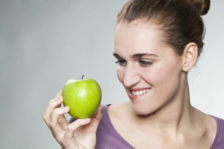 mesmerized: happy beautiful young woman biting lips to resist in eating appetizing green apple for symbol of beauty and healthy nutrition