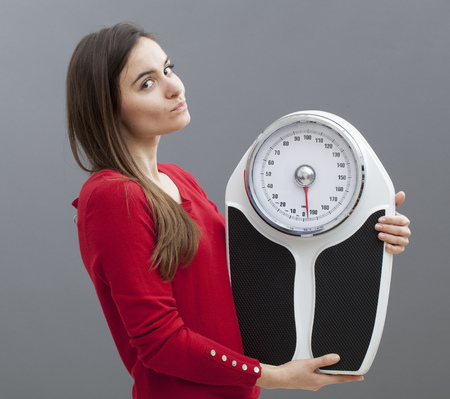 satisfied young woman with weighting scale in hands for concept of weight loss or weight control
