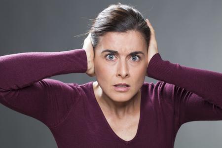 oreja: el estrés y el miedo concepto - 30s infeliz mujer con el pelo marrón que cubre sus oídos del ruido, protegiendo a sí misma, tiro del estudio
