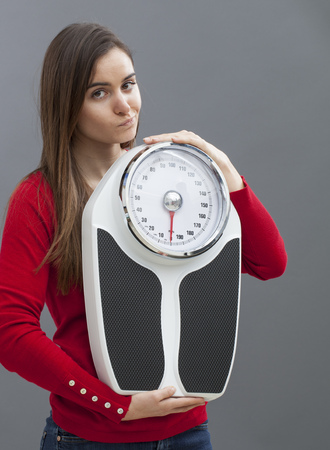 skeptical: skeptical young woman with weighting scale in hands for concept of weight loss or weight control