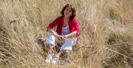 aging woman: female casual relaxation - lonely aging woman sitting in high dry summer field for relaxation and peaceful silence from the city,summer daylight Stock Photo