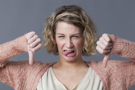 decepci�n: concepto decepci�n - disgustado mujer joven con el pelo rubio rizado haciendo doble pulgares hacia abajo con la cara divertida para el desaliento y la infelicidad