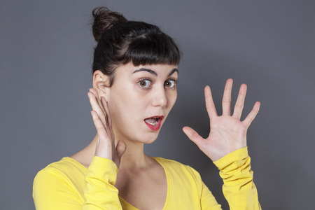eyes wide open: surprise and fear concept - portrait of surprised 20s woman with yellow sweater with both hands up for amazement and eyes wide open,studio shot