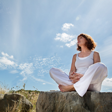 senior zen - relaxing senior yoga woman sitting on a stone seeking for harmony and balance outdoors with a beautiful blue sky for future retirement,low angle view