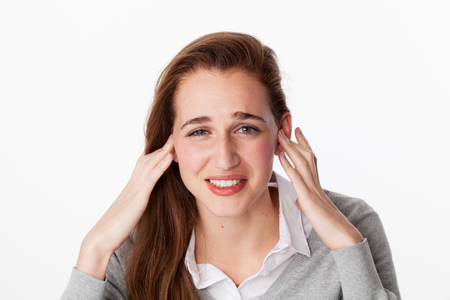 on a white background: tinnitus concept - sick young woman having painful headache,covering closed ears,annoyed by loud noise not wanting to hear their side of story