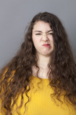 grinding teeth: unhappiness and disappointment concept - young overweight woman with long brown hair expressing concern with a funny face for fun complain,studio shot