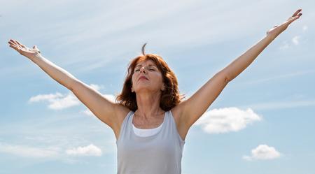 mujeres mayores: zen alto - pensando hermosa mujer madura abrir su chakra y los brazos, buscando armonía y bienestar al aire libre en la luz del día verano