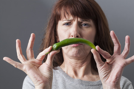 aversion: frowning mature woman upset in holding green pepper for spicy aversion