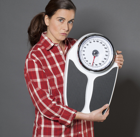 30s: casual 30s woman skeptical about her scales for weight loss