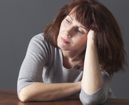persona deprimida: hermosa mujer mayor que se reclina la cara en sus manos que se establecen en una mesa en la reflexión sobre el envejecimiento