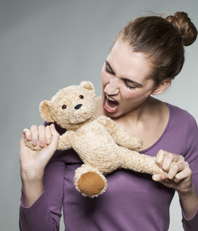 angry teddy: furious young woman torturing teddy bear for growing up or teenager nervous breakdown