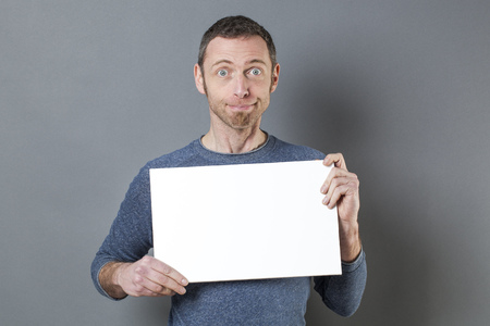40s: fun 40s casual man holding a copy space white board for good surprising announcement Stock Photo