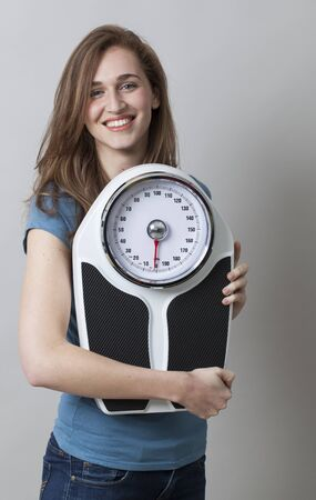 20s: satisfied 20s woman holding her weight scale for weight control