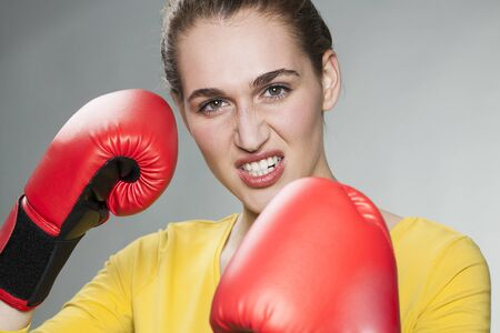 conflicting: conflicting young woman defending herself with boxing gloves for competition concept