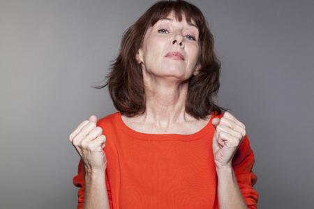 arrogancia: el concepto de �xito - hermosa mujer madura que llevaba un su�ter de color naranja expresar su poderosa arrogancia y la actitud snob con la barbilla hacia arriba para los negocios