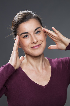 acupressure hands: radiant 30s woman smiling in practising face acupressure with hands on face and temples for natural eye care and facial contour exercise