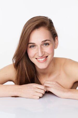 desnudo: feliz mujer joven que presenta para ablandar el cuidado de la piel y fortalecer el cuidado del cabello en el fondo blanco
