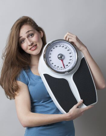 kilos: surprised young woman displaying her kilo or pound loss