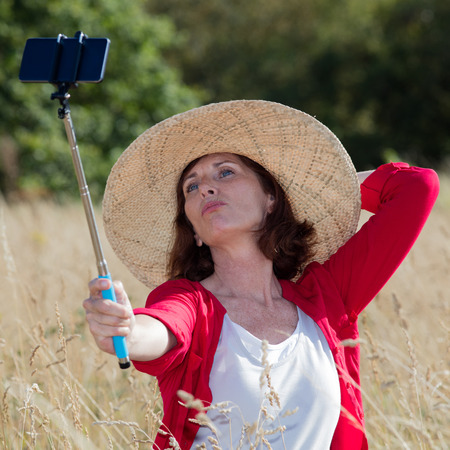 aging woman: mature selfie concept - sexy aging woman enjoying taking a selfie with a stick in summer dry meadows wearing a summer hat,natural daylight Stock Photo